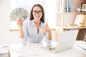 girl holding money and giving thumbs up