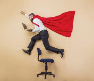 man with Superman cape leaps over steno chair with his laptop open in his hands