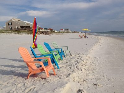 4 colorful adirondack chairs on empty beach